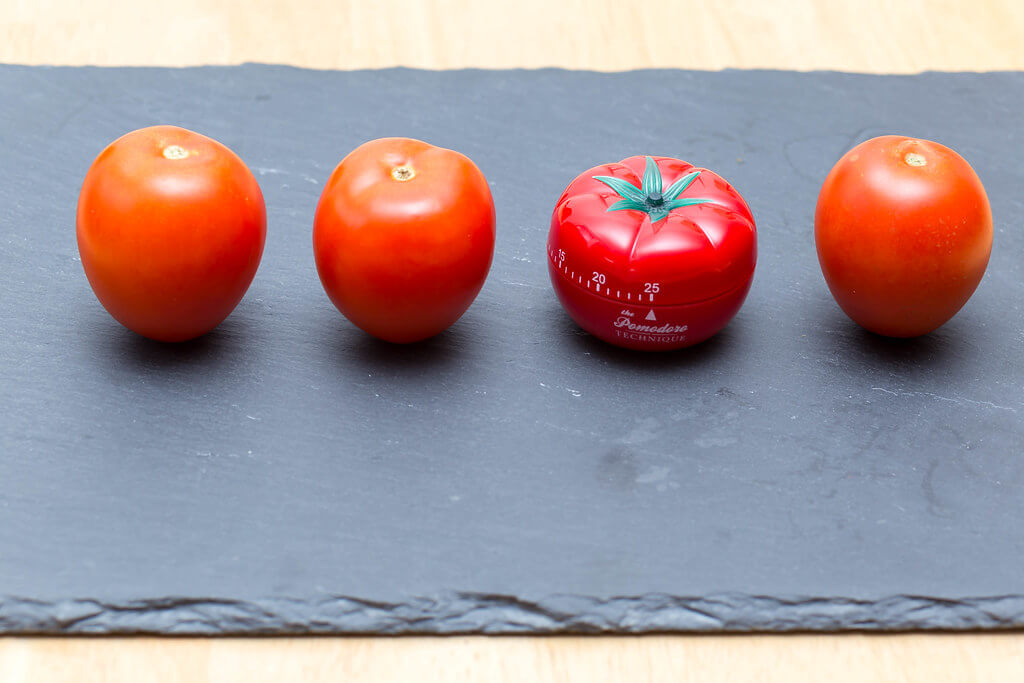 Pass the tomatoes sitting on a slate cutting board for the red Pomodoro timer to help you set time management goals