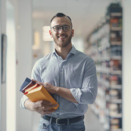 Smiling man in library holding a stack of books