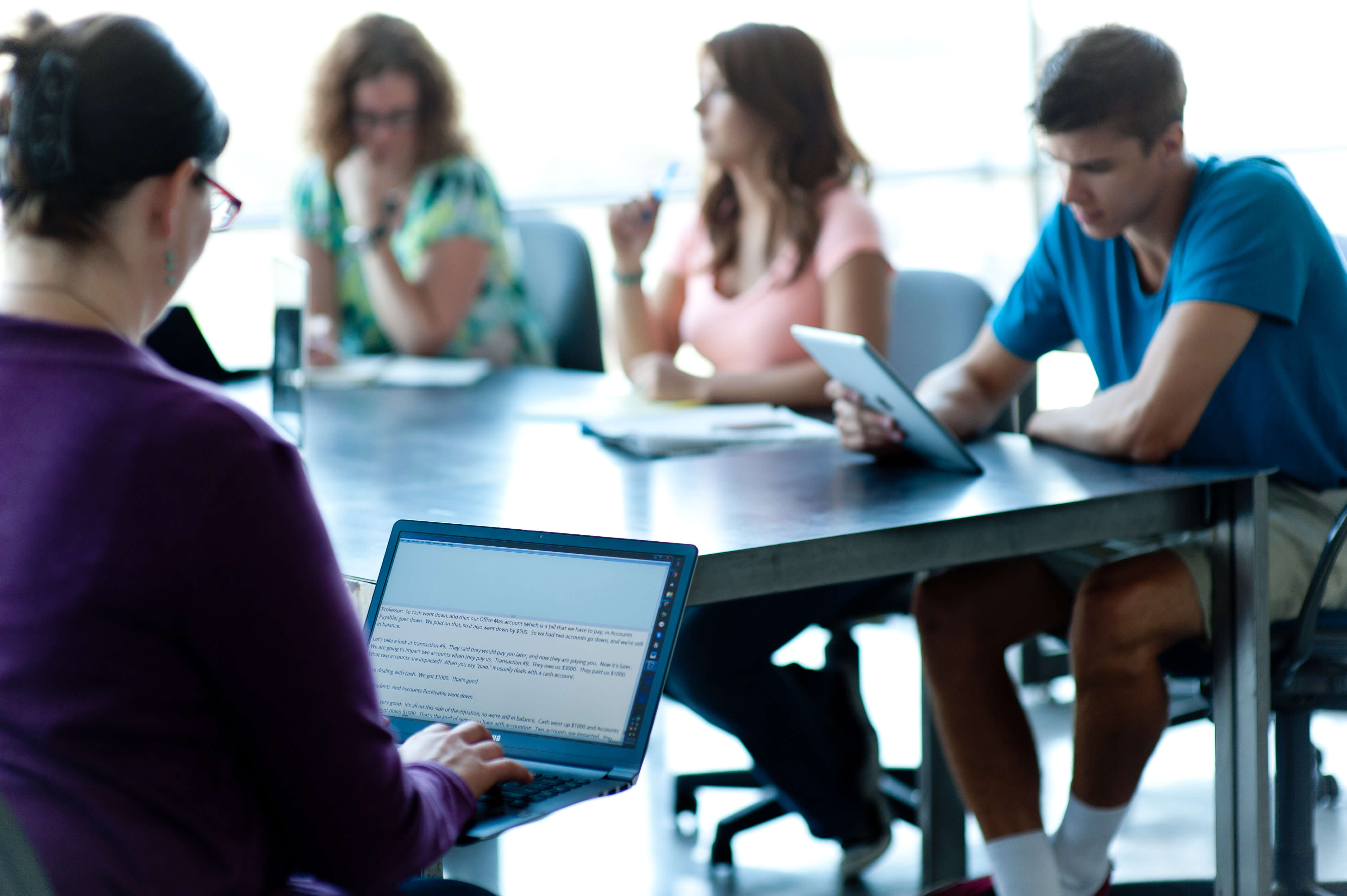 transcriber typing on a laptop while a group of students are talking, with one student reading text from an ipad