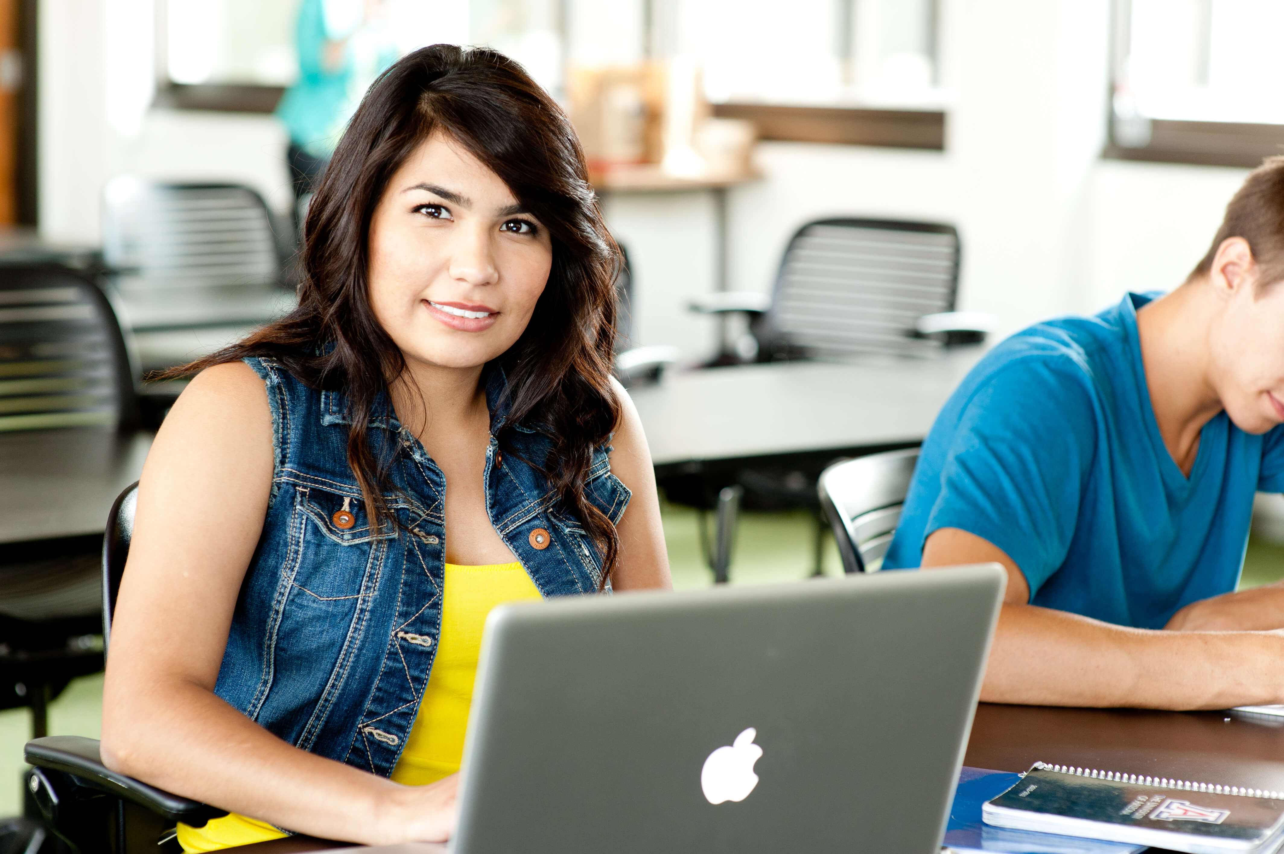 close-up of young woman sitting on front of laptop smiling