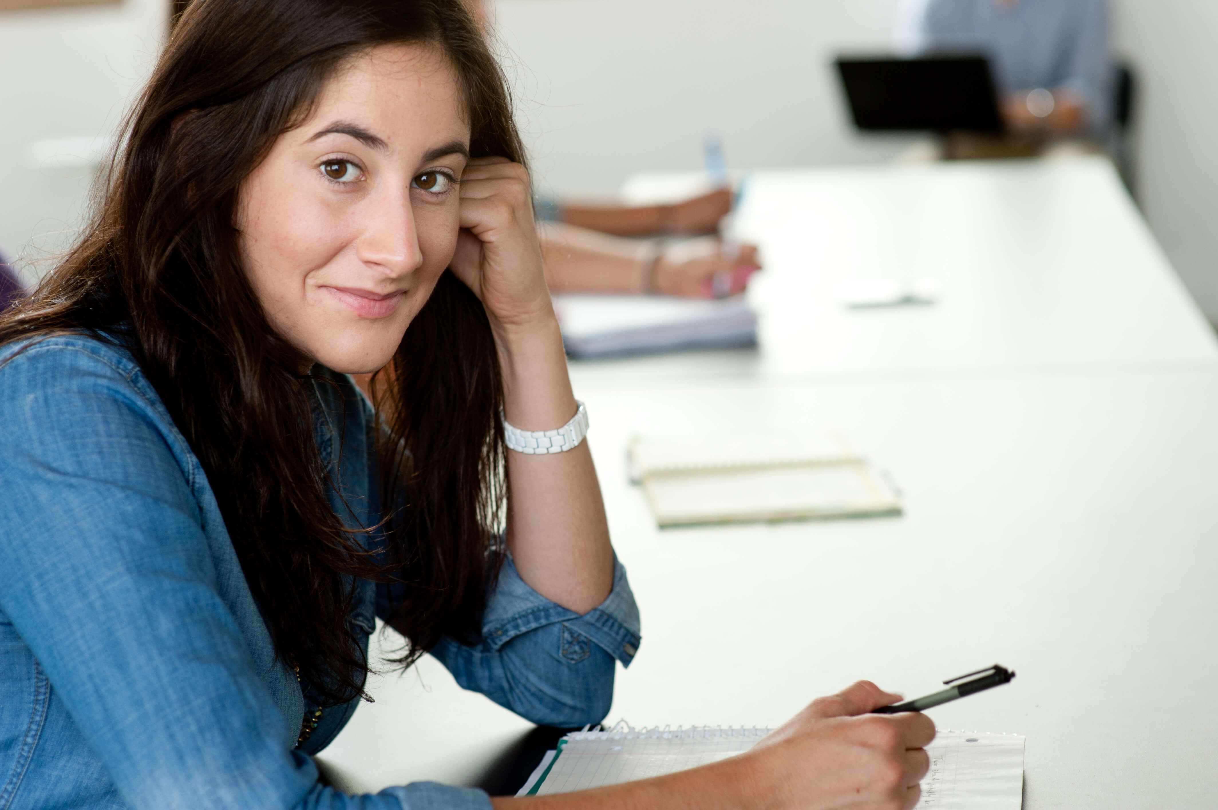 close-up photo of woman with long dark hair sitting at classroom table smiling