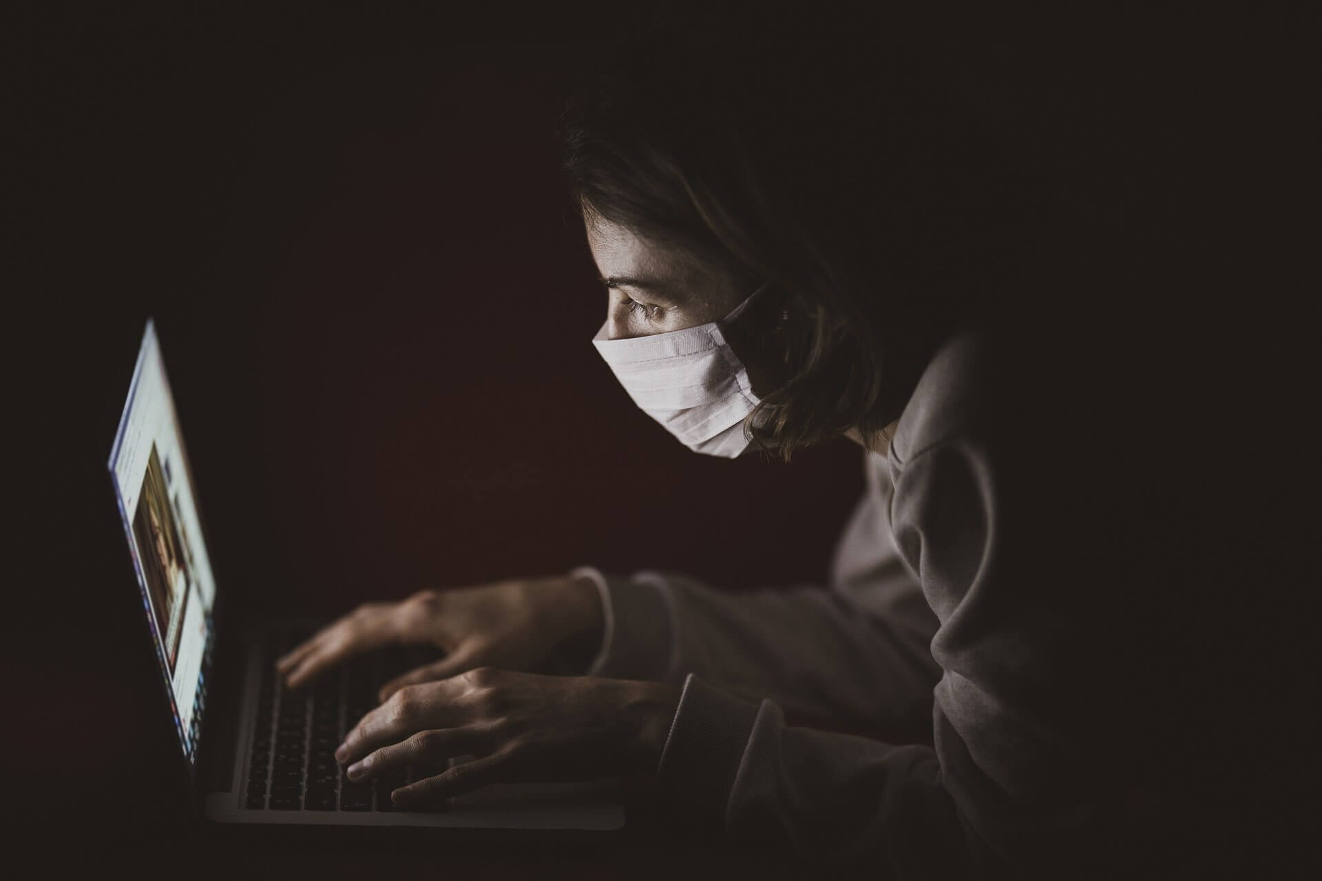 person typing on a laptop while sitting in the dark wearing a surgical mask like those worn during COVID-19 pandemic
