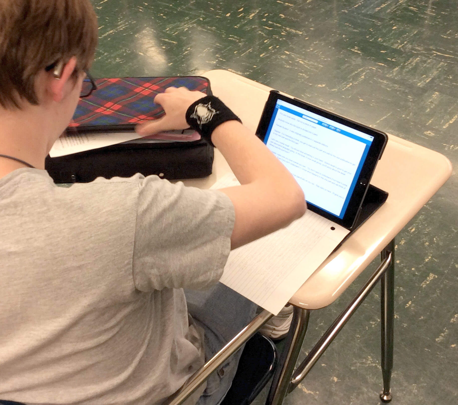 student sitting at his desk reading a TypeWell transcript on his iPad