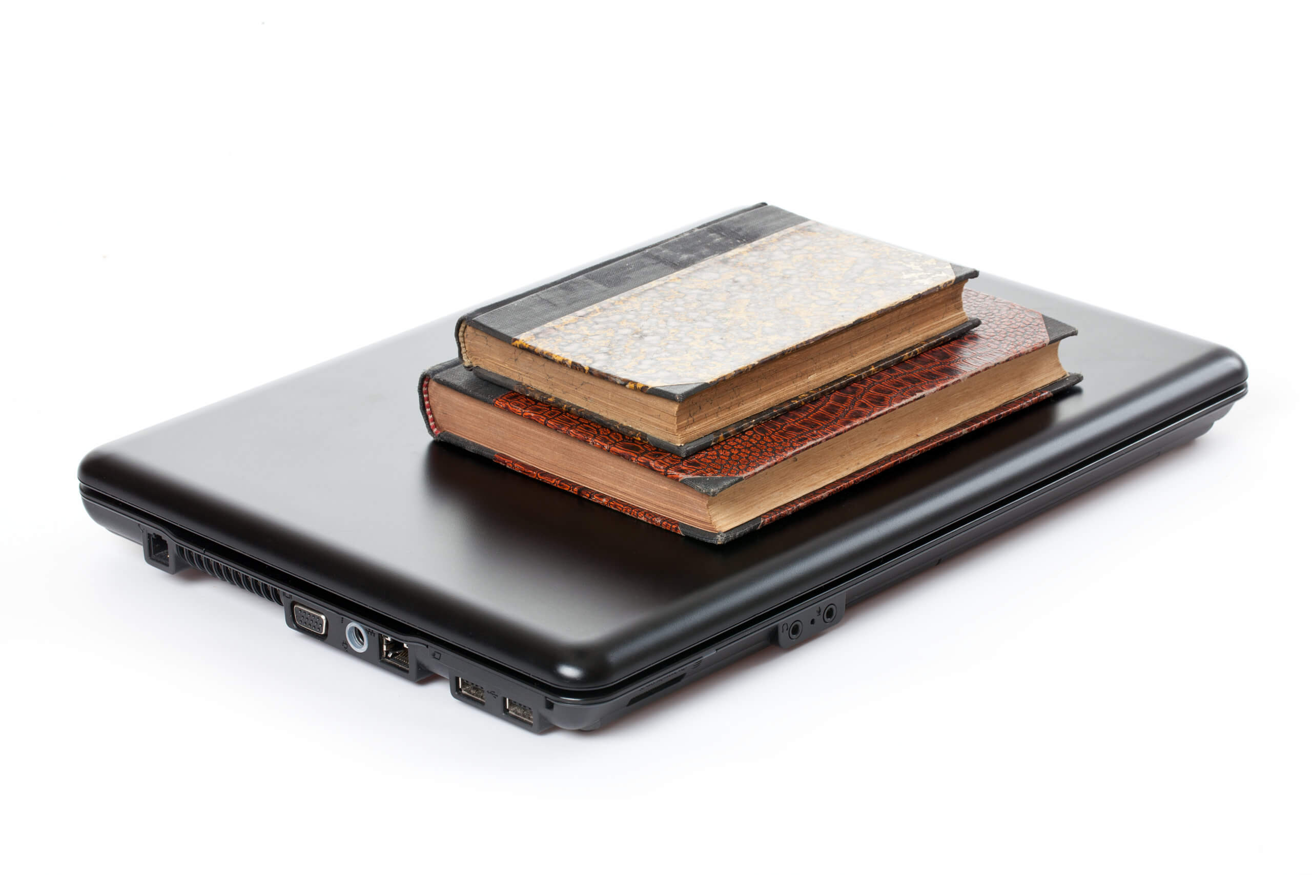 old books and laptop on white background