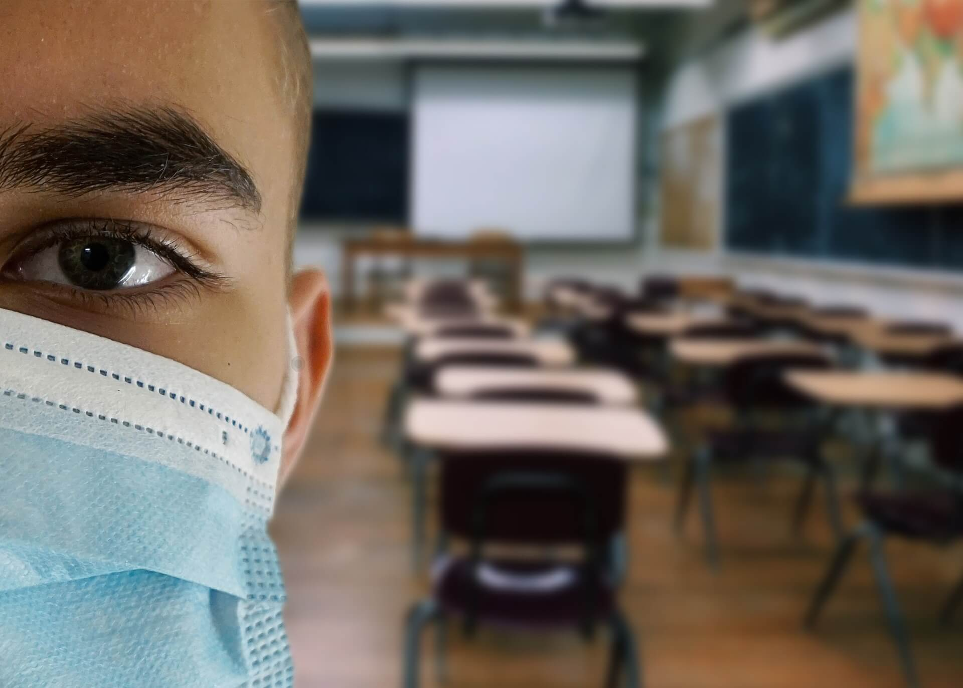 man in an empty classroom wearing a surgical mask like those worn during the coronavirus pandemic