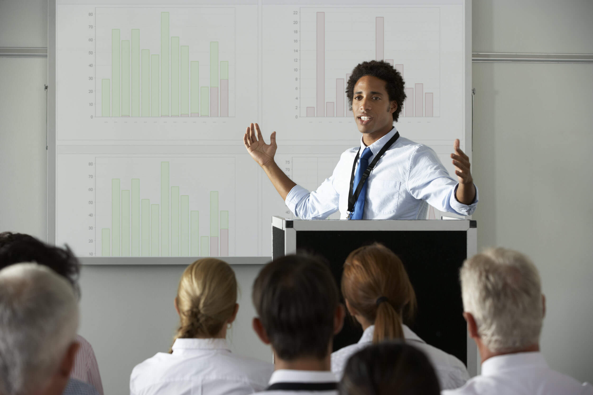 Young businessman delivering presentation at a conference in which real-time transcription services may require prep time